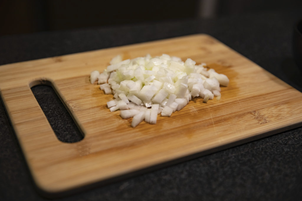 A diced onion sitting on a bamboo cutting board.