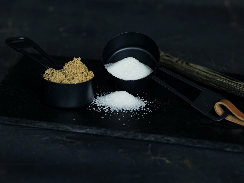 Measuring cups with brown and granulated sugar for simple syrup recipe