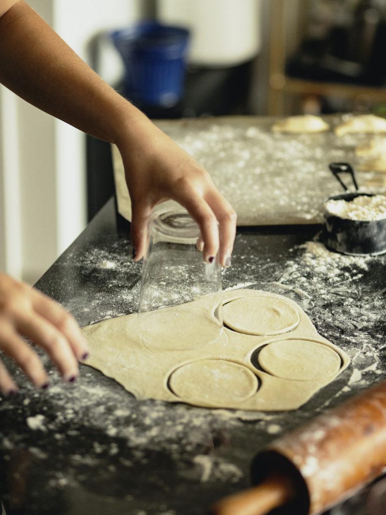 Hands cutting pierogi dough